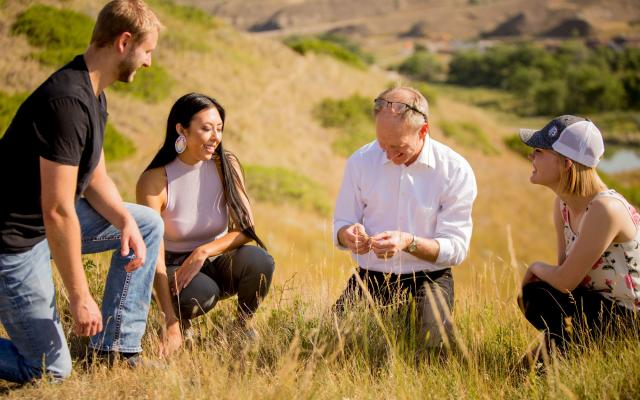 Roy Golsteyn in coulee grass with students